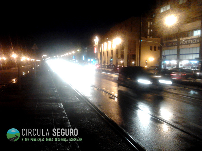 Chuva nocturna e o reflexo das luzes no asfalto molhado